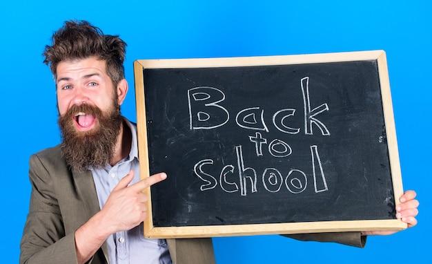 勉強する準備はできていますか。先生は勉強に戻ることを宣伝し、学年を始めます。新しい学年の準備をします。先生のひげを生やした男は立って、学校の青い背景に黒板の碑文を保持します。