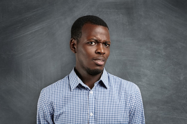 真剣ですか?市松模様のシャツを着たイライラした若い浅黒い教師または学生、不満で驚いて、広告用のコピースペースのある黒板に敵対している