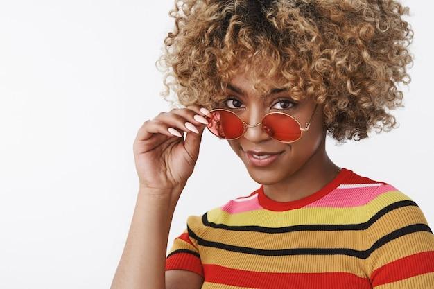Sei serio. ritratto di donna afroamericana carina interrogata e dubbiosa che si toglie gli occhiali da sole e guarda da sotto la fronte insicura, sorridendo come se rassicurasse e facendo domande
