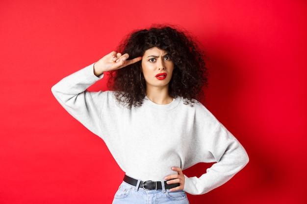 너 바 보니. 곱슬 머리를 가진 짜증나고 혼란스러운 소녀, 머리를 가리키고 사람이 미친 듯하거나 이상하게 꾸짖고 붉은 벽에 서서