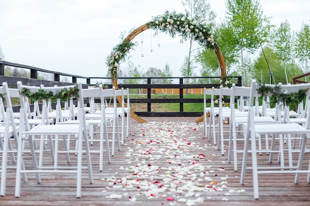 Area of the wedding ceremony in forest, near river on the pier