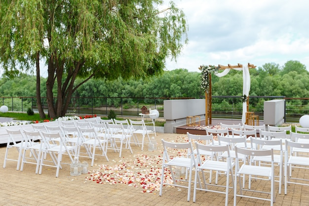 Area of the wedding ceremony near river on pier wooden arch white chairs decorated with flowers
