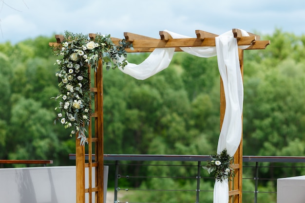 Area of the wedding ceremony near river on the pier. wooden rectangular arch, white chairs decorated with flowers, greenery, petals, eucalyptus and tulle. cute, trendy rustic decor
