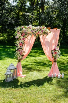 Area of the wedding ceremony in the park wooden rectangular arch rustic decor