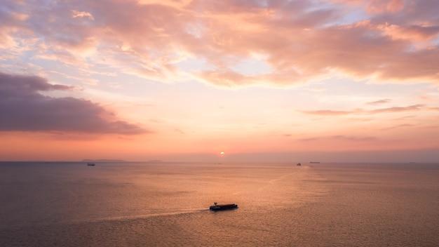 Плоский вид на морской пейзаж и небольшой контейнеровоз, плывущий в море в вечернем розовом небе