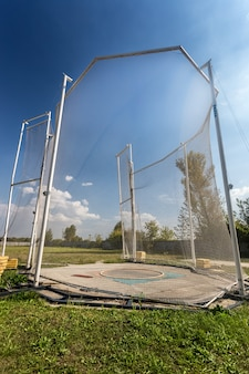 Arena for throwing hammer surrounded by high safety net
