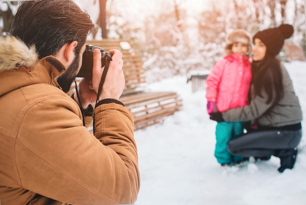 Arenthood, fashion, season and people concept - happy family with child in winter clothes outdoors. take photos with each other