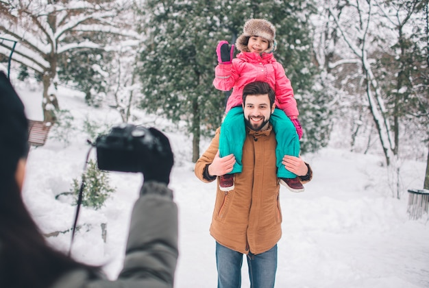 Arenthood, fashion, season and people concept - happy family with child in winter clothes outdoors. take photos with each other.
