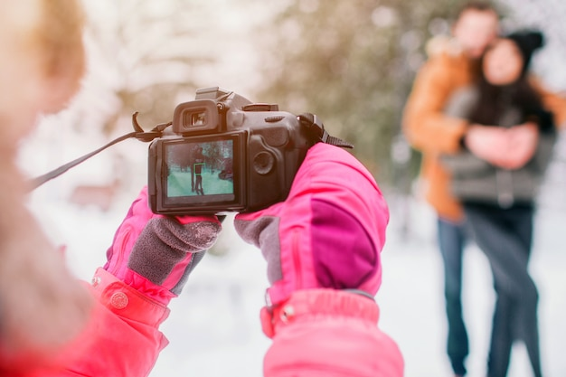 Концепция arenthood, моды, сезона и людей - счастливая семья с ребенком в зиме одевает outdoors. делайте фотографии друг с другом