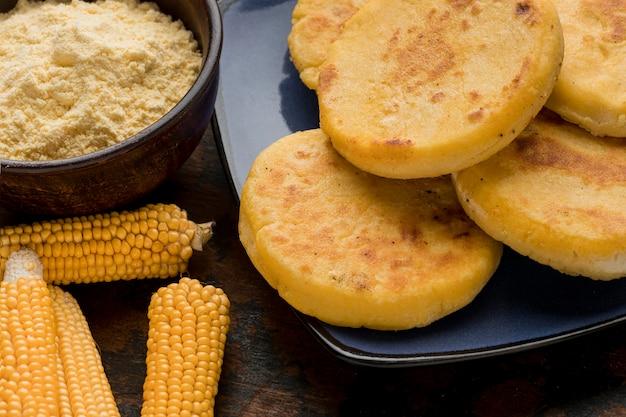 Арепы на тарелке и сырая кукуруза