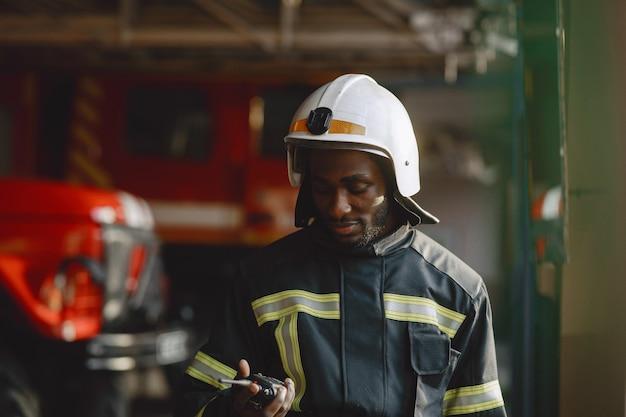 제복을 입은 arfican 소방관. 남자는 일을 준비합니다. 남자는 라디오 송신기를 사용합니다.