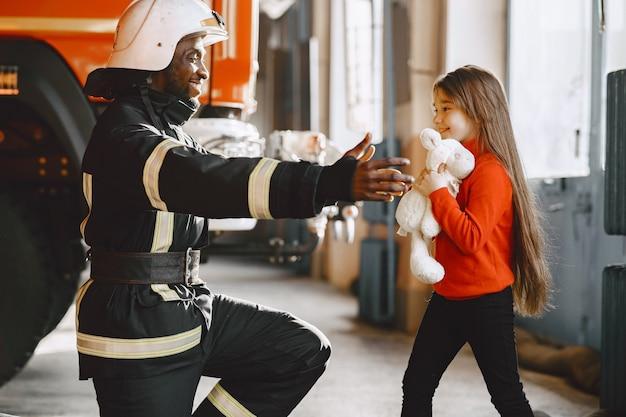 Арфиканский пожарный в форме. человек готовится к работе. парень с ребенком.