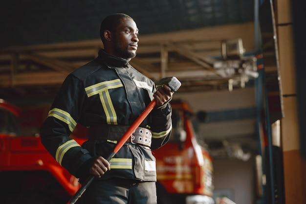 Арфиканский пожарный в форме. человек готовится к работе. парень с молотком.