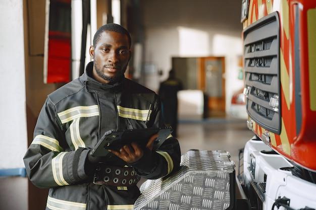 Арфиканский пожарный в форме. человек готовится к работе. парень с планшетом.