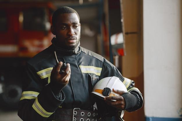 Arfican fireman in a uniform. man prepare to work. guy use radio transmitter.