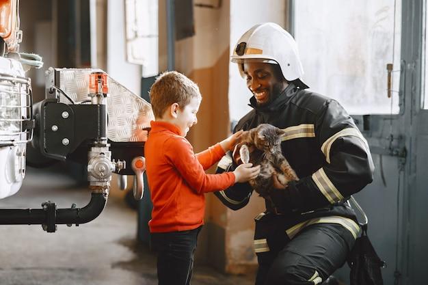 Vigile del fuoco arfican in uniforme. l'uomo si prepara a lavorare. ragazzo con bambino.