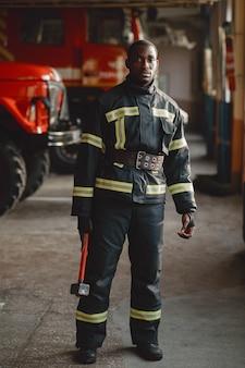 Vigile del fuoco arfican in uniforme. l'uomo si prepara a lavorare. ragazzo con hummer.