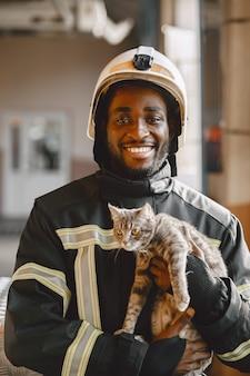 Vigile del fuoco arfican in uniforme. l'uomo si prepara a lavorare. ragazzo con gattino.