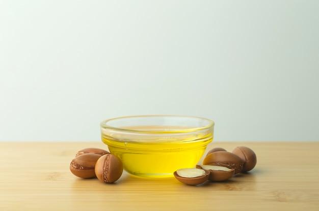 Орехи арганы и масло на деревянном столе