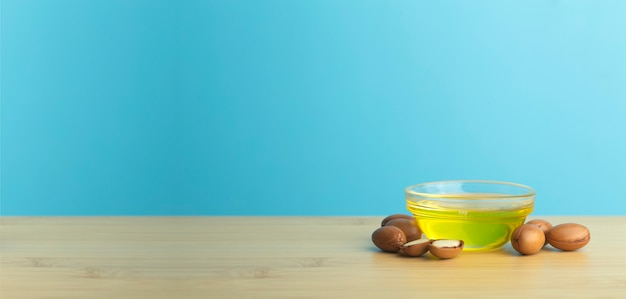 Argan nuts and oil on a wooden table