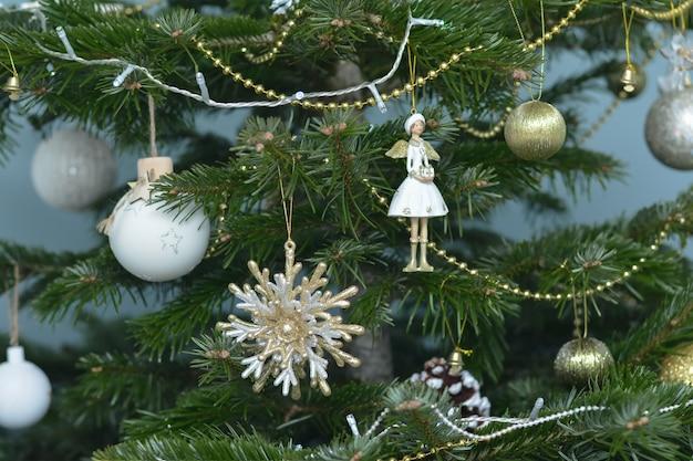 은빛 금색과 흰색과 크리스마스 트리에 매달려 있는 장난감