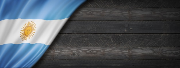 Argentina flag on black wood wall. horizontal panoramic banner.