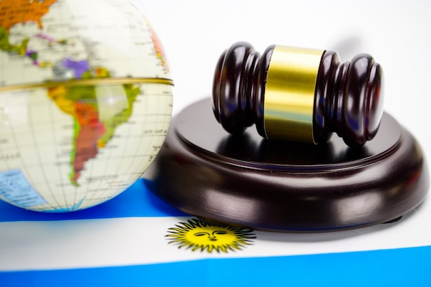 Argentina flag and judge hammer with globe world map. law and justice court concept.