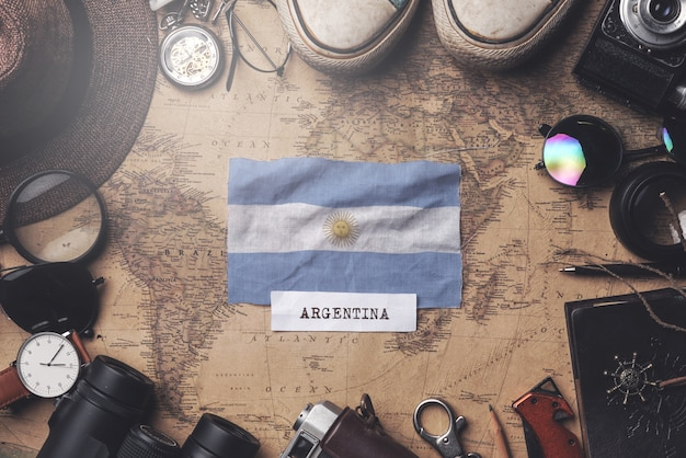 Argentina flag between traveler's accessories on old vintage map. overhead shot