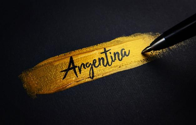Argentina handwriting text on golden paint brush stroke