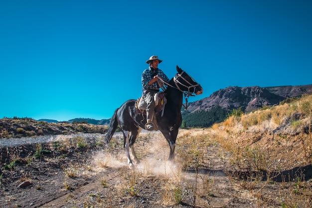 アルゼンチンのカウボーイ(ガウチョ)がパタゴニアでカメラを通り過ぎて馬を歩きます。
