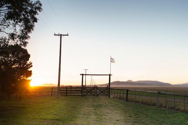 Аргентинский сельский пейзаж со старым флагом, развевающимся у ворот