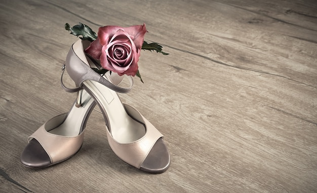 Argentine tango shoes and a rose on a wooden floor