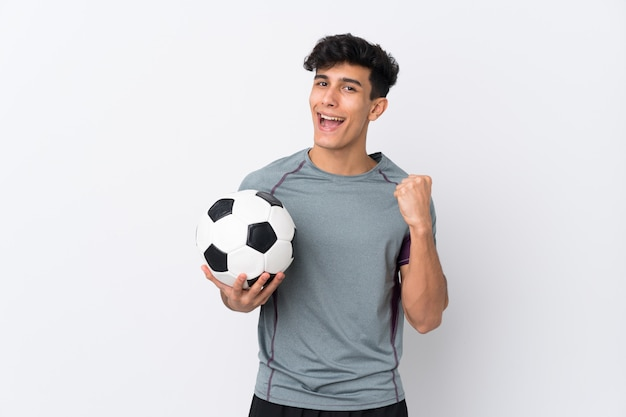 Argentinian football player man over isolated white wall celebrating a victory