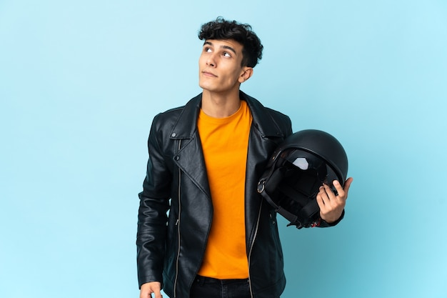 Аргентинский мужчина в мотоциклетном шлеме и смотрит вверх