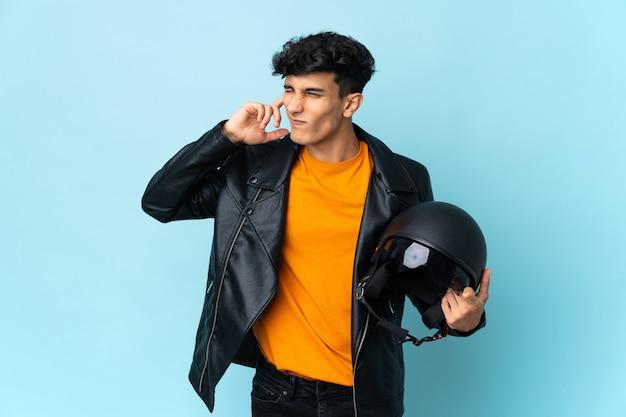 欲求不満と耳を覆っているオートバイのヘルメットを持つアルゼンチンの男