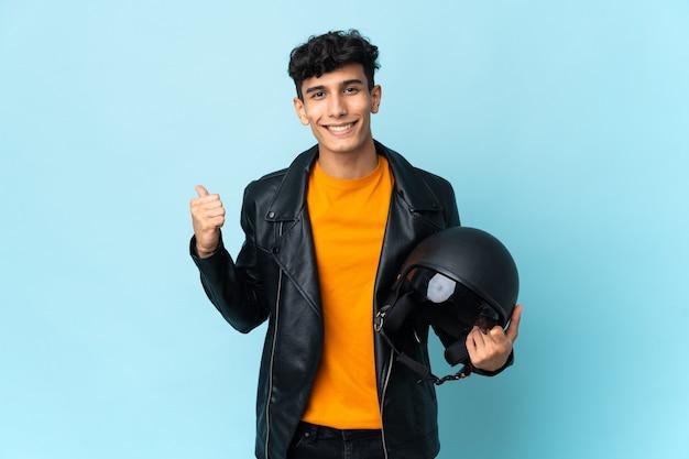 제품을 제시하기 위해 측면을 가리키는 오토바이 헬멧을 쓴 아르헨티나 남자