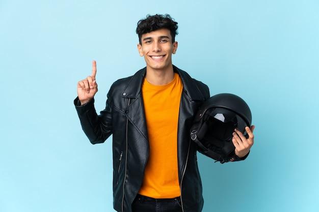 좋은 아이디어를 가리키는 오토바이 헬멧을 가진 아르헨티나 남자