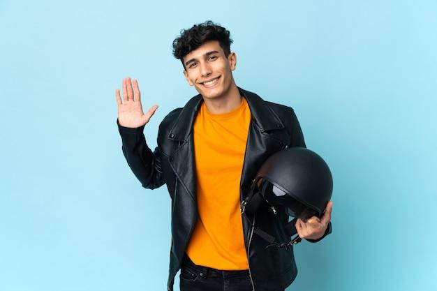 幸せな表情で手で敬礼するオートバイのヘルメットを持つアルゼンチンの男