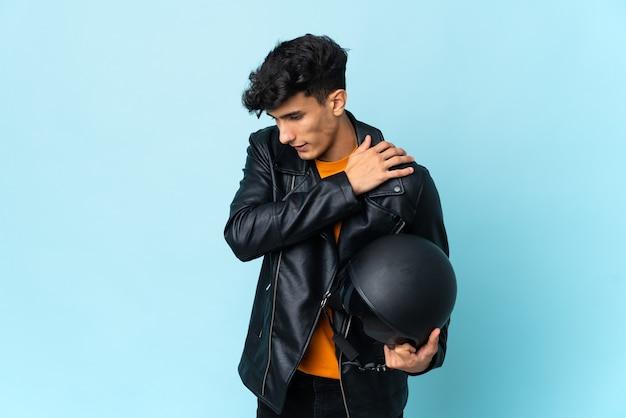 Аргентинец в мотоциклетном шлеме страдает от боли в плече из-за того, что приложил усилие