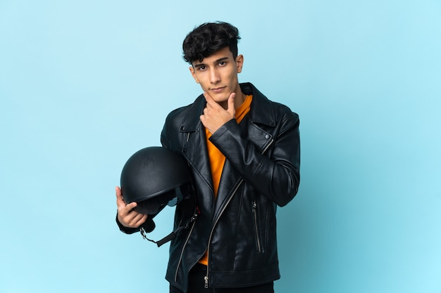 Аргентинский мужчина в мотоциклетном шлеме думает