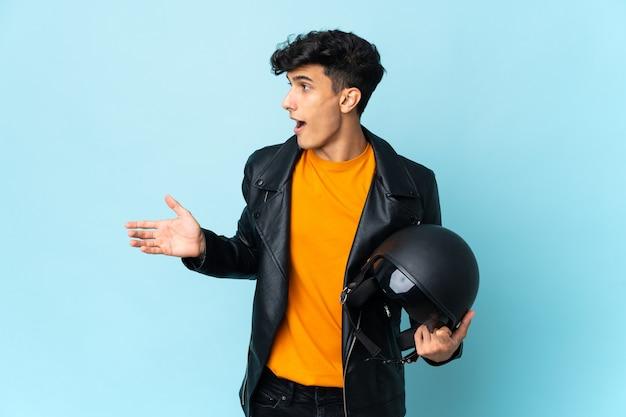 측면을 보면서 놀라운 표정으로 오토바이 헬멧을 가진 아르헨티나 남자