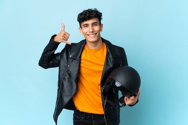 Argentinian man with a motorcycle helmet making phone gesture. call me back sign