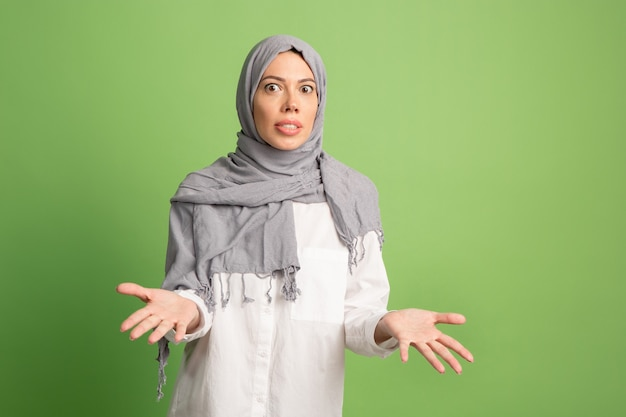 Argue, arguing concept.arab woman in hijab. portrait of girl, posing at green studio background. young emotional woman. the human emotions, facial expression concept. front view.