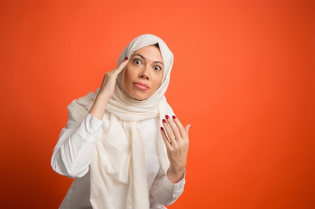 Argue, arguing concept.arab woman in hijab. portrait of girl, posing at. red studio background. young emotional woman. the human emotions, facial expression concept. front view.
