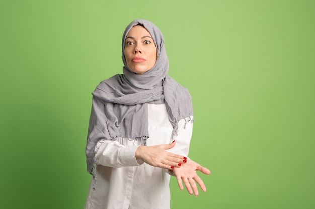 主張し、concept.arab女性をヒジャーブで主張します。緑のスタジオの背景でポーズをとって、女の子の肖像画。若い感情的な女性。人間の感情、表情のコンセプト。正面図。