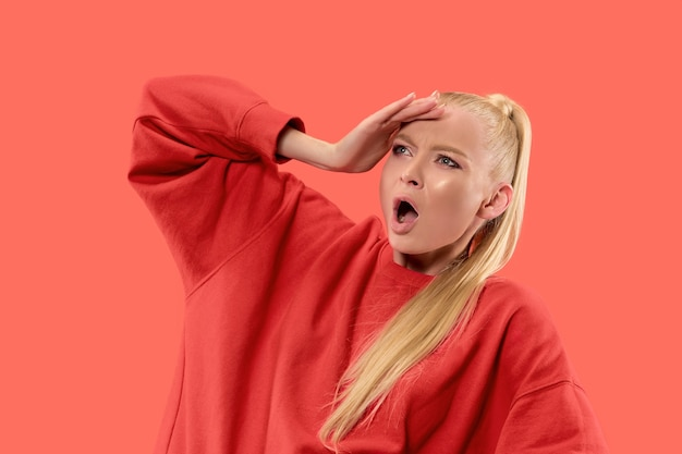 議論し、概念を主張します。コーラルスタジオの背景に分離された美しい女性のハーフレングスの肖像画。カメラを見て若い感情的な驚きの女性。人間の感情、表情の概念