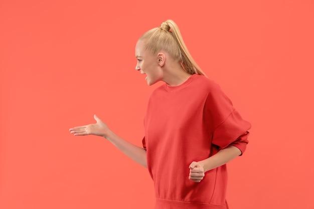 논쟁, 논쟁 개념. 산호 스튜디오 backgroud에 고립 된 아름 다운 여성 절반 길이 초상화. 카메라를보고 젊은 감정적 인 놀된 여자 인간의 감정, 표정 개념