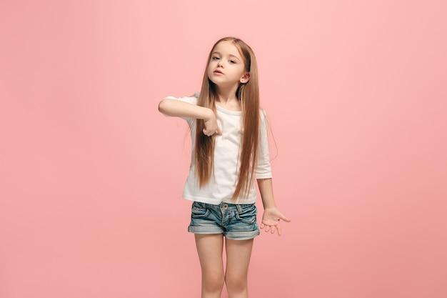 議論、議論の概念。ピンクで隔離の美しい女性のハーフレングスの肖像画。カメラを見ている若い感情的な十代の少女