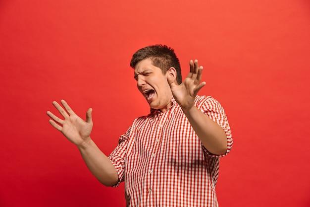 Argomenta, sostenendo il concetto. ritratto a mezzo busto maschio divertente isolato sul backgroud rosso dello studio. giovane uomo sorpreso emotivo che guarda l'obbiettivo. emozioni umane, concetto di espressione facciale. vista frontale
