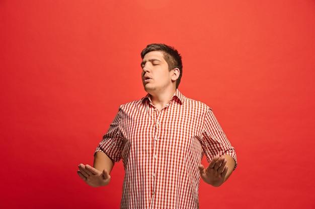 Argomenta, argomentando il concetto. ritratto a mezzo busto maschio divertente isolato sul backgroud rosso dello studio. giovane uomo sorpreso emotivo che guarda l'obbiettivo